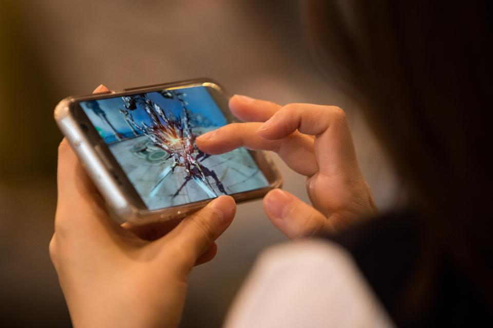 A Netmarble Games Corp. employee plays the Lineage 2 Revolution mobile game on a smartphone.